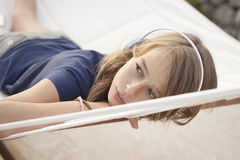 Girl with headphones relaxing in hammock royalty free stock images
