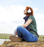 Girl with headphones at rock near lake. Stock Photo