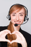 Girl with headphones shows heart. Royalty Free Stock Image