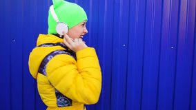 Girl with headphones singing and dancing to music, smiling happy girl listening music in headphones. stock video