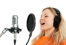 Girl in headphones singing with studio microphone. Female singer in headphones singing with studio microphone. Isolated on white background stock photo