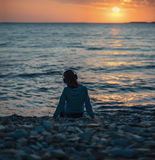 Girl in headphones sitting on beach on sunset Stock Photography