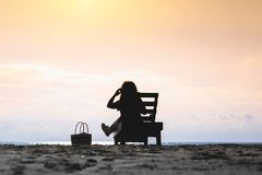 Girl in headphones is sitting on the sun lounger listening to music on the beach at sunset. stock photography