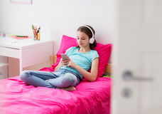 Girl in headphones and smartphone at home Royalty Free Stock Images