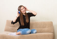 Girl in headphones. Smiling pretty girl in headphones sitting on a couch Royalty Free Stock Images