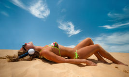 Girl with headphones sunbathing in summertime stock image