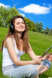 Girl with headphones and a tablet in the park. Stock Images