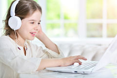 Girl in headphones using laptop Royalty Free Stock Image