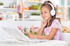 Girl in headphones using laptop Stock Images