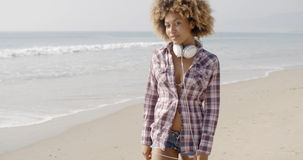 Girl With Headphones Walking On The Beach Stock Photo