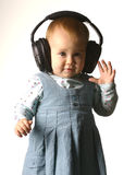 The girl with headphones on a white background. Baby, business, child, clothing, computer, cute, dress, education, expression, face, fashion, fun, games, hair Royalty Free Stock Photos