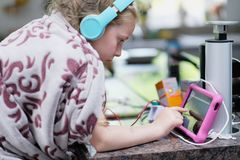 A girl with headphones wrapped in a fleece blanket royalty free stock photography