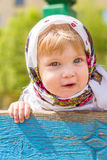 Girl in a headscarf. Little girl leaning on fence Stock Images