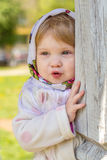 Girl in a headscarf. Little girl peeks out from behind the column Stock Image
