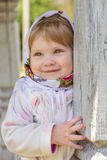Girl in a headscarf. Little girl peeks out from behind the column Stock Photo