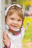 Girl in a headscarf. Little girl peeks out from behind the column Royalty Free Stock Photography