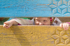 Girl in a headscarf. Little girl in a headscarf shows finger peeping through a fence Stock Image