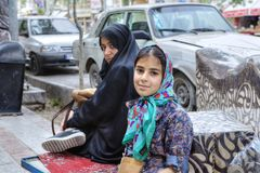 Girl in headscarf and woman in chador rest in street, Iran. Stock Photo