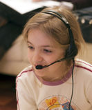 Girl and headset. A young girl with headset on, sitting in front of her computer Stock Photo