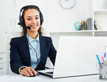 Girl with headset and laptop in office Royalty Free Stock Photography