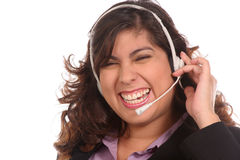 Girl in headset is laughing at request. Girl in white headset is enjoying the conversation as she laughs at your request Stock Photography
