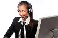Girl with a headset works at the computer Stock Photo