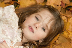 Girl headshot in Leaves. Young girl lying on her back in the leaves Royalty Free Stock Image