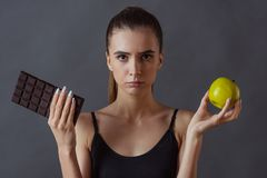 Girl and healthy eating. Beautiful girl in sportswear is holding an apple and a bar of chocolate and looking at camera, on gray background royalty free stock photos