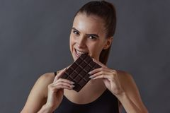 Girl and healthy eating. Beautiful girl in sportswear is biting a chocolate bar and looking at camera, on gray background stock photo