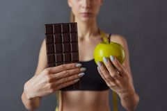 Girl and healthy eating. Cropped image of beautiful girl in sportswear holding an apple and a bar of chocolate, on gray background stock images