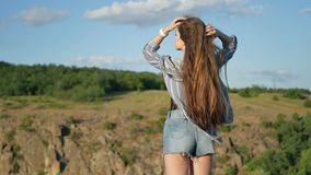 A girl with healthy, long hair. Walks on the nature with a beautiful view of the rocks stock video footage
