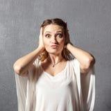 Girl in hear no evil pose. Girl posing as hear no evil monkey in studio stock image