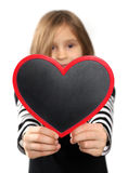 Girl with heart. Little girl is keeping the blackboard in the shape of a heart Stock Image