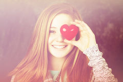 Girl with heart. Beautiful girl holding a heart in front of her eye Royalty Free Stock Photography