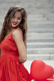 Girl with a heart. Smiling girl in red dress holding heart behind Stock Image