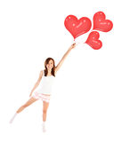 Girl with heart balloons. Image of cute female flying on red heart-shaped balloons, laughing woman isolated on white background, freedom lifestyle, Valentine day Stock Image