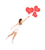 Girl with heart balloons. Image of cute female flying on red heart-shaped balloons, smiling woman isolated on white background, freedom lifestyle, Valentine day Stock Photo