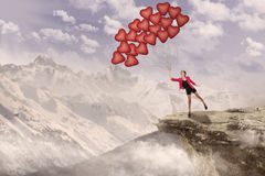 Girl and heart balloons on mountain Stock Photos
