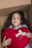 Girl with heart box. Smiling child girl laying in carton box with big red heart Royalty Free Stock Image