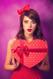 Girl with heart shape gift. Beautiful brunette girl with heart shape gift on violet background Royalty Free Stock Photography