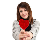 Girl with a heart-shaped candy Stock Photography