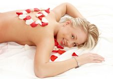 Girl with heart-shaped petals in massage salon Royalty Free Stock Photography