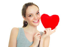 Girl with a heart-shaped pillow Stock Image