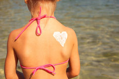 Girl with heart-shaped sun cream on the back. Toned image Royalty Free Stock Images