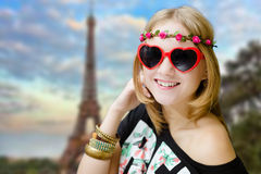 Girl in heart shaped sunglasses on blurred Eiffel Stock Image