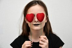 Girl with hearts in front of her eyes. Teenage girl with black painted lips covers her eyes with two  red hearts Royalty Free Stock Images