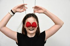 Girl with hearts in front of her eyes. Teenage girl with black painted lips covers her eyes with two  red hearts Stock Photography