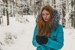Girl heated with a cup of tea or coffee in the winter forest. Hot mulled wine in cup. Happy winter time in winter park. Woman heated with hot tea Royalty Free Stock Photo
