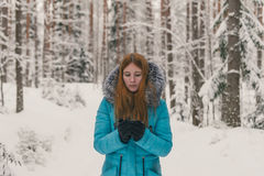 Girl heated with a cup of tea or coffee in the winter forest. Hot mulled wine in cup. Happy winter time in winter park. Woman heated with hot tea Royalty Free Stock Images