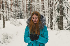Girl heated with a cup of tea or coffee in the winter forest. Hot mulled wine in cup. Happy winter time in winter park. Woman heated with hot tea Stock Image